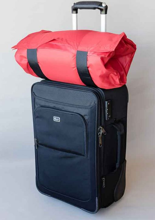 Red SleepKeeper on top of hand luggage